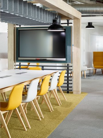 Yellow and white naughtone Viv Wood Chairs arranged neatly around a large white Dalby Conference Table in a very open meeting space.