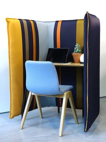 A light blue naughtone Viv Wood Chair stationed at a colourfully striped Cloud 1.5 Desk, and viewed from the back.