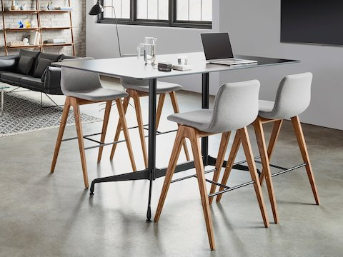 Four light gray Viv Wood Stools with walnut bases are around a rectangular Eames Standing Height table in black. The scene is set in front of a lounge space and white walls.