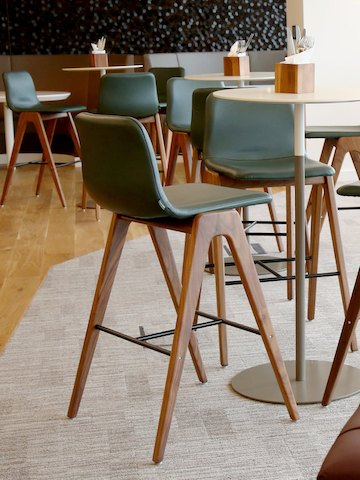 Green naughtone Viv Wood Stools placed around multiple standing height pedastal tables.