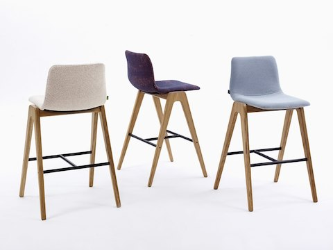 A white, a dark purple, and a light blue naughtone Viv Wood Stool arranged at various angles.