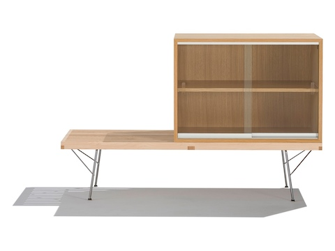 A Nelson Basic Cabinet Series storage module with one shelf and sliding glass doors sits atop a Nelson Platform Bench.