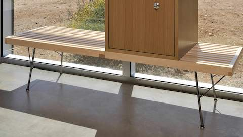 A closed storage module from the Nelson Basic Cabinet Series sits atop a Nelson Platform Bench that abuts a glass wall.