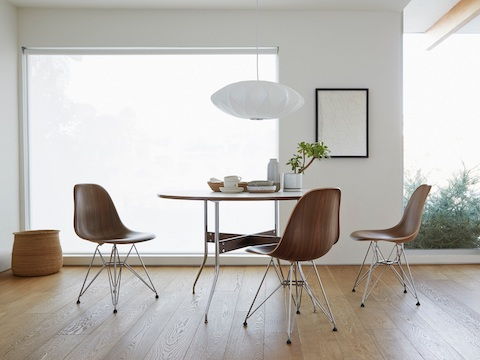 A Nelson Bubble Pendant lamp overhangs a Nelson Swag Leg Table surrounded by three Eames Molded Wood Chairs.