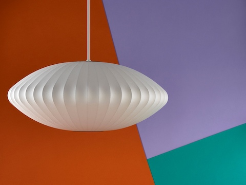 A Nelson Saucer Bubble Pendant lamp hanging in front of an orange, purple, and green background.