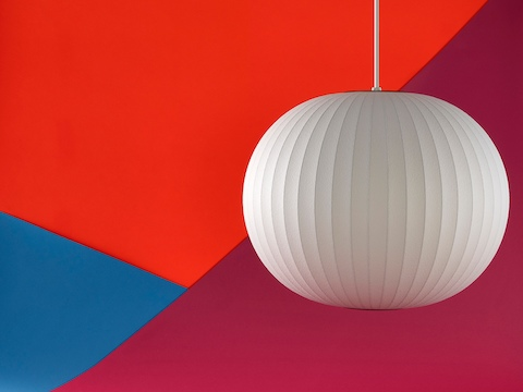 A Nelson Ball Bubble Pendant lamp hanging in front of an orange, red, and blue background.