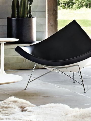 A black leather Nelson Coconut Lounge Chair on an outdoor patio.