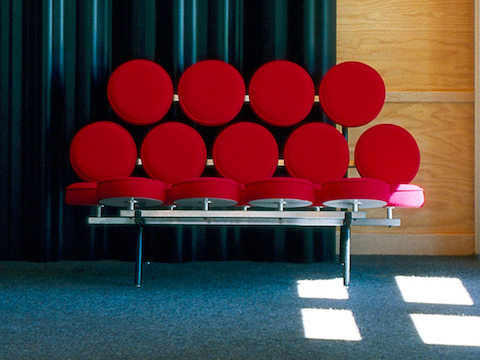 A Nelson Marshmallow Sofa upholstered in red fabric and situated in front of a blue curtain.