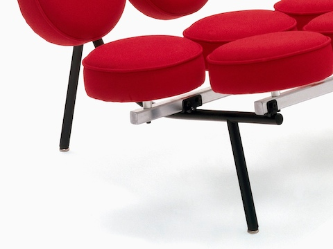 Close view of a red upholstered Nelson Marshmallow Sofa, showing how the round cushions attach to the frame.