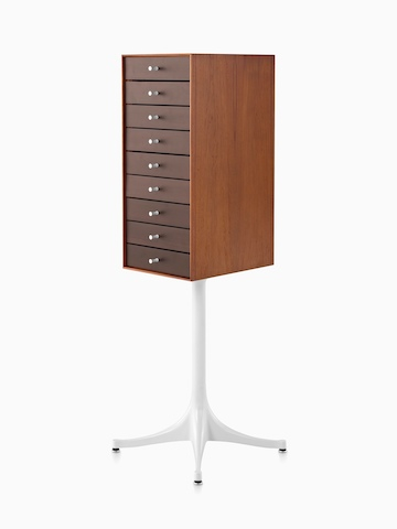 Angled view of a vertical nine-drawer Nelson Miniature Chest with a medium finish and white pedestal base.