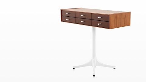 Angled view of a horizontal six-drawer Nelson Miniature Chest with a medium finish and white pedestal base.