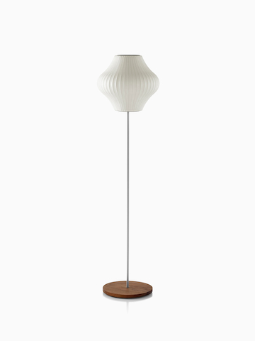A white Nelson Pear Lotus Floor Lamp with a walnut-covered steel base and the smaller of two available shades.