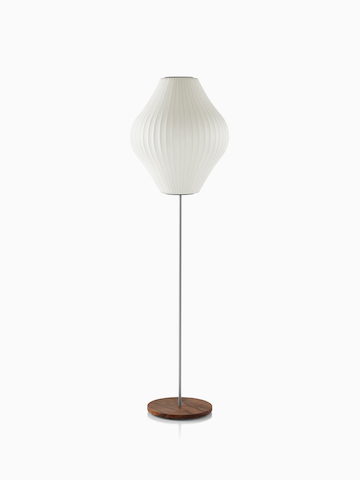 A white Nelson Pear Lotus Floor Lamp with a walnut-covered steel base and the larger of two available shades.