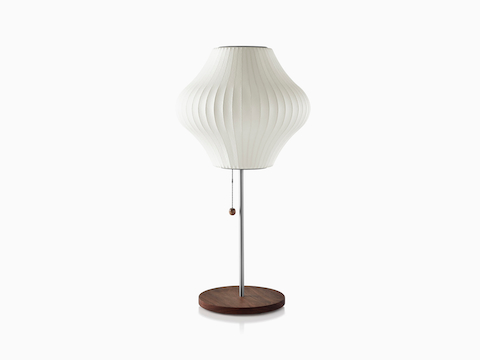A white Nelson Pear Lotus Table Lamp with a walnut-covered steel base.