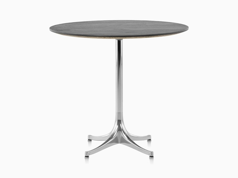 A round Nelson Pedestal Table with a black top and polished aluminum base.