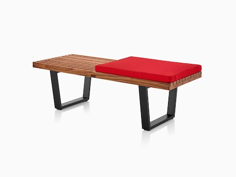 Walnut Nelson Platform Bench with black wood legs and red padded seat, viewed from the front at an angle.