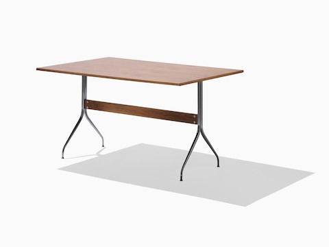 A rectangular Nelson Swag Leg Table in a medium wood finish, showing a single walnut stretcher between tubular steel legs.
