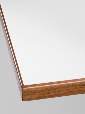 Close-up of the corner detail on a Nelson Swag Leg Table with a white laminate top and walnut veneer edge band.