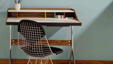 A residential workspace outfitted with an Nelson Swag Leg Desk and an Eames Wire Chair with a black bikini pad.
