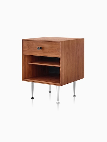 An angled view of a Nelson Thin Edge bedside table with a medium finish, black knob, and slim aluminum legs.
