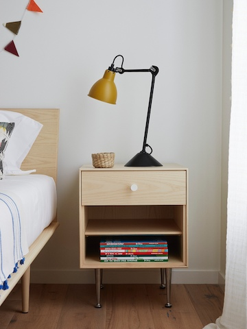 A lamp sits atop a Nelson Thin Edge bedside table positioned next to a bed.
