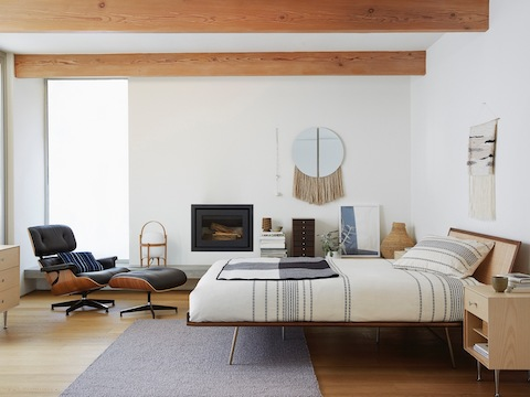 A Nelson Thin Edge bedside table in a contemporary bedroom that also features an Eames Lounge Chair and Ottoman.