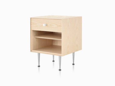 An angled view of a Nelson Thin Edge bedside table with a light finish, white knob, and slim aluminum legs.