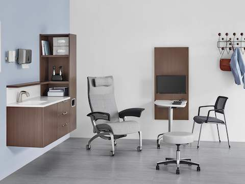 Exam room with Mora casework on the wall in a dark brown finish, and an Intent table located between a patient chair and side chair.