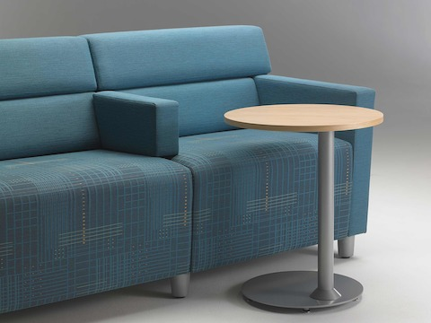 A close-up view of a Steps Lounge System in blue textile and a Steps round end table with a powder-coated base and laminate top.