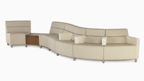 A low-back Steps Lounge System in a curved configuration in a light-colored textile.