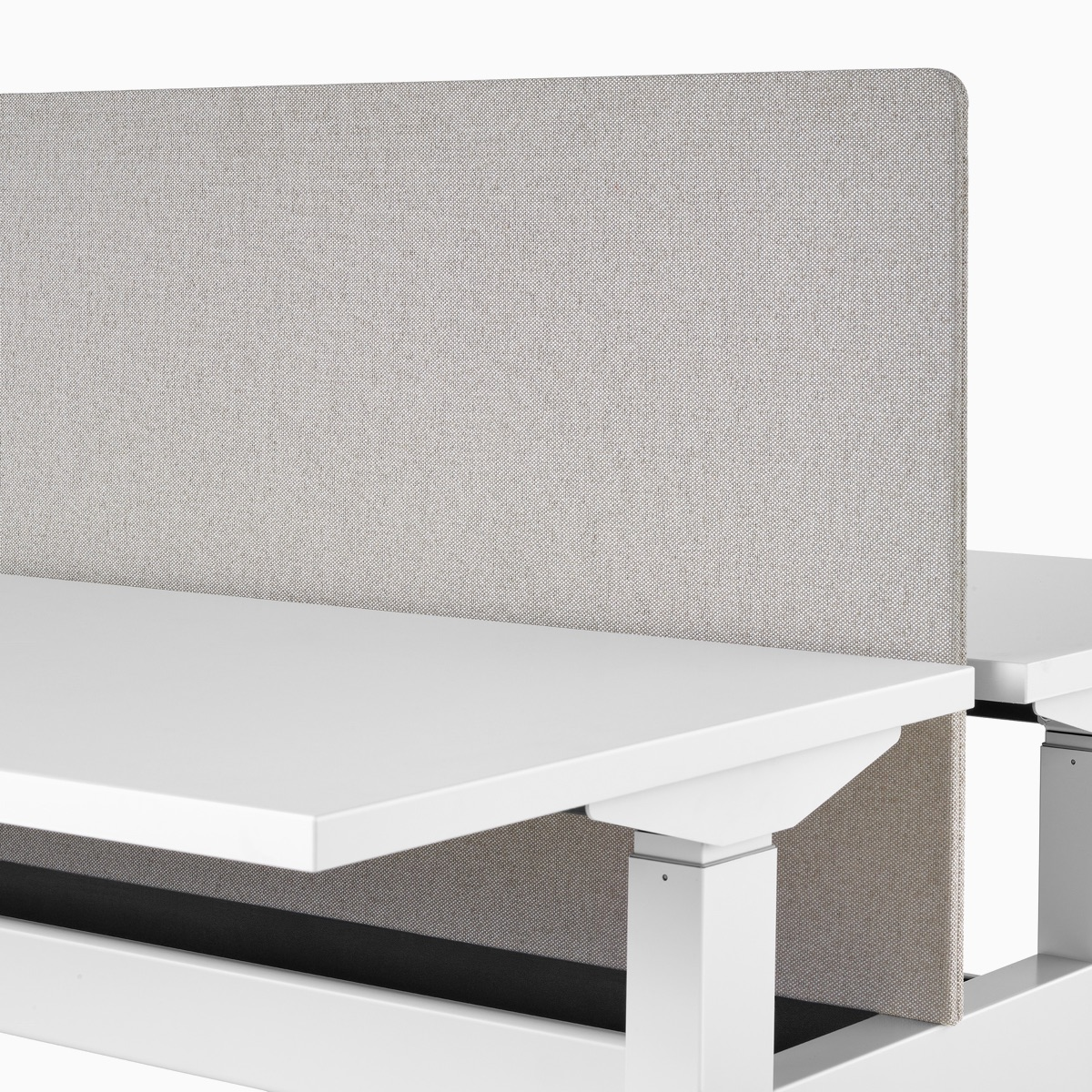 A close-up view of a gray fabric screen attached to the surface of a Nevi Link standing desk system.