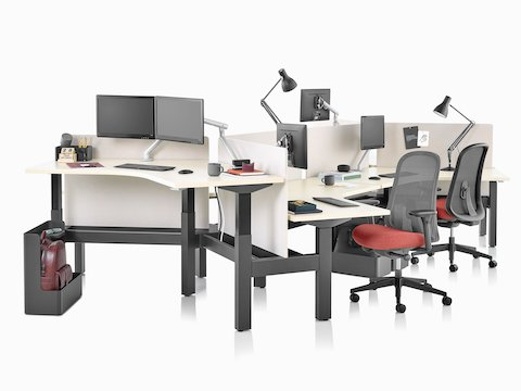 A Nevi Link standing desk with black legs and 120-degree work surfaces, red and black Lino office chairs, and white screens. Two of the six desks are raised to standing height.