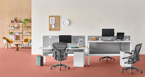 An office setting with a Nevi Link standing desk system in the foreground with white rectangular work surfaces and black Aeron office chairs, and a lounge area with Eames shell chairs and bookcase in the background. One of the four desks is raised to standing height.