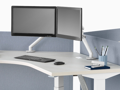 A close-up view of a Nevi Link standing desk system with 120-degree work surfaces and light blue screens. One of the three desks is raised to standing height.