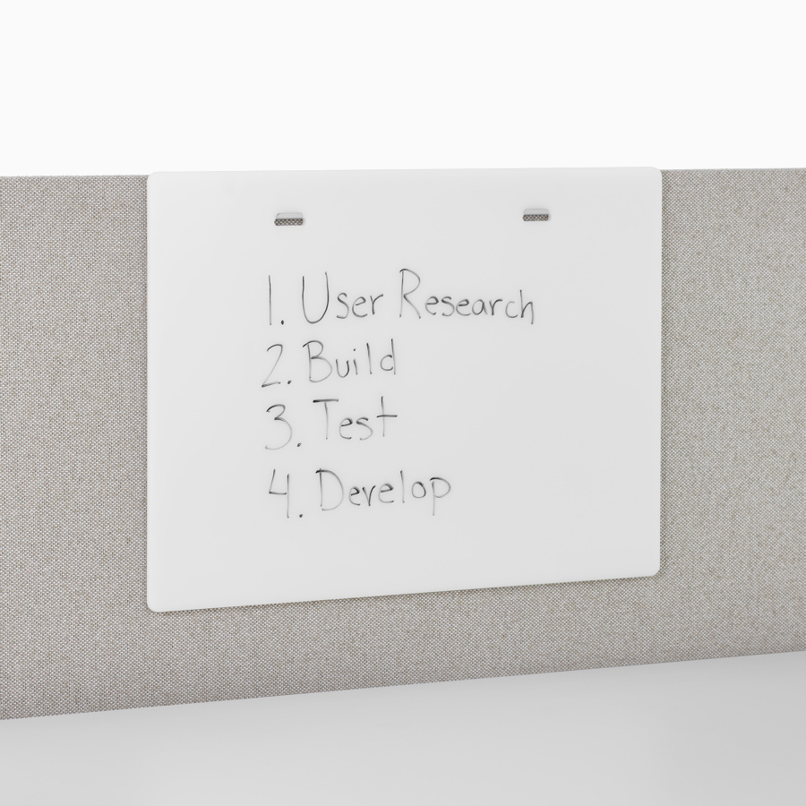 A close-up view of a markerboard accessory with writing on it.