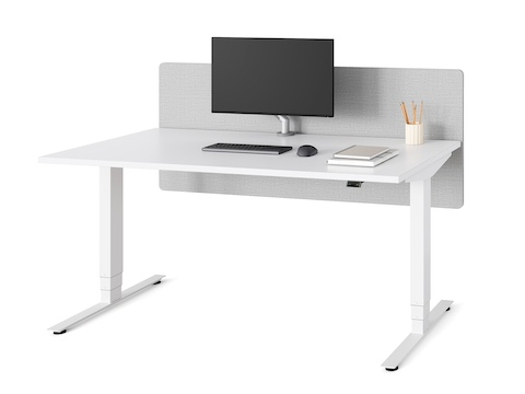 A white Nevi Sit-Stand Desk with a grey privacy screen, in the seated height position.