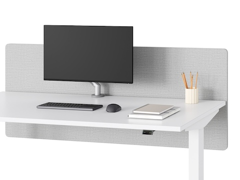 A close-up view of a white Nevi Sit-Stand Desk with a grey privacy screen.