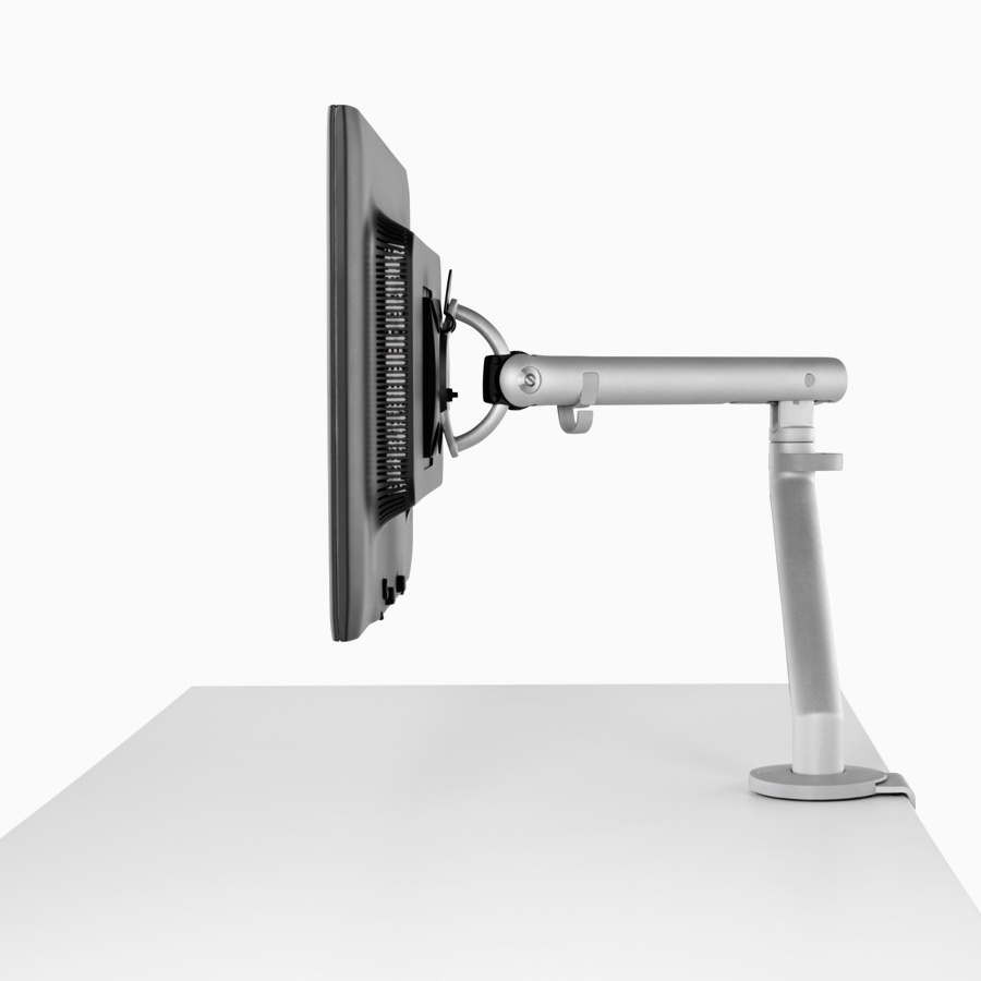 A computer monitor supported by a silver Flo Monitor Arm.