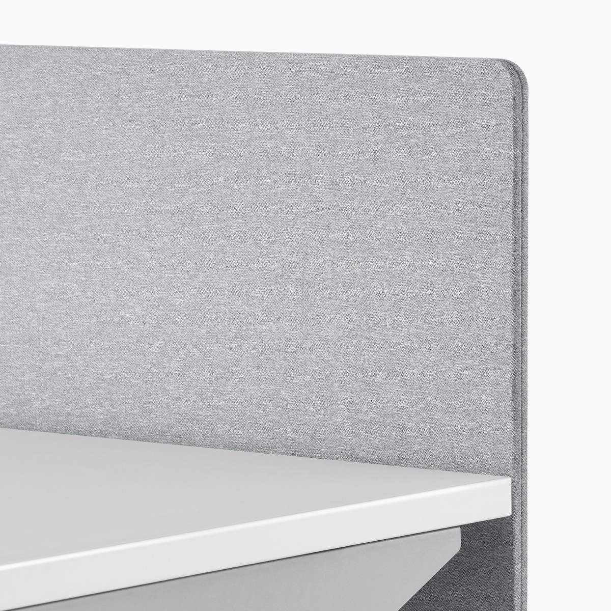 A close-up view of a gray fabric screen attached to the surface of a Nevi standing desk.