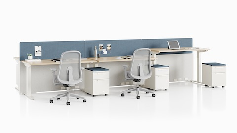 Nevi standing desks integrated with Canvas Channel with blue screens, white Tu Storage units, and gray Lino office chairs.