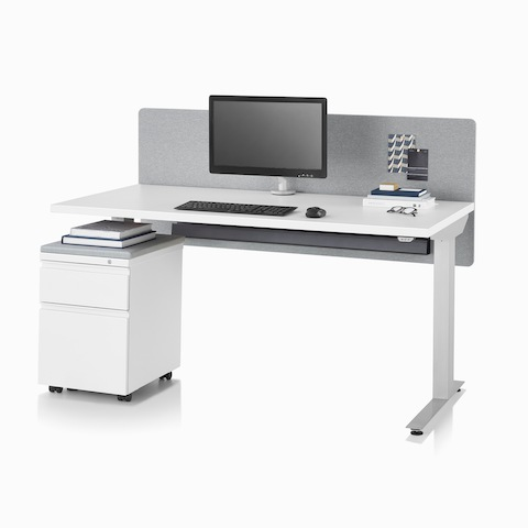 A Nevi standing desk with a white surface, silver legs, gray fabric screen, Flo monitor arm, and a mobile storage unit.