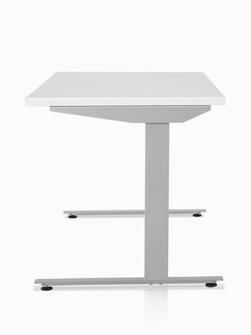 A side view of a Nevi standing desk with a white surface and silver legs.
