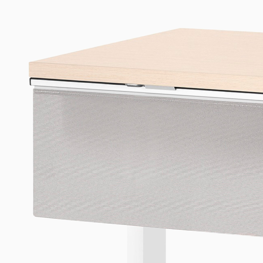 A close-up view of a gray modesty panel attached to the surface of a Nevi standing desk.