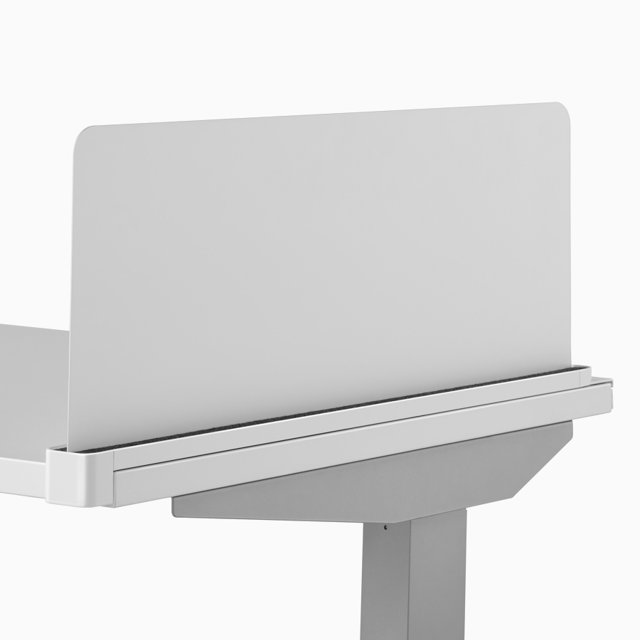 A close-up view of a gray Ubi screen attached to the side of a Nevi standing desk's surface.