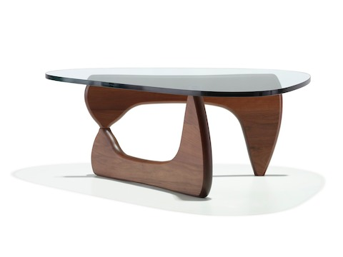 A Noguchi occasional table with a freeform glass top and curved wood base in a medium finish.