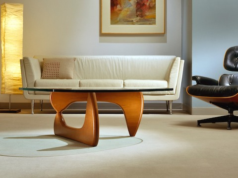 A Noguchi occasional table complements an ivory-colored Goetz Sofa and black Eames Lounge Chair.