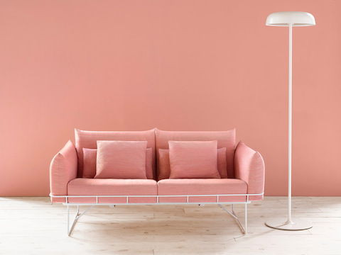 A white Ode floor lamp next to a salmon-colored Wireframe Sofa.