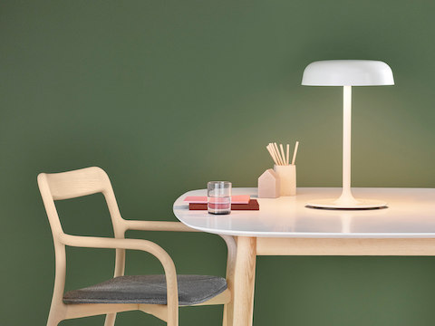 A white Ode table lamp illuminates a white-top table and side chair.