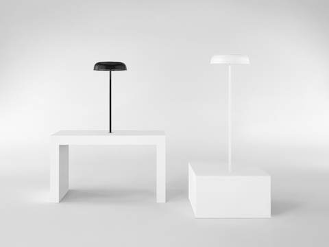 Black and white Ode Lamps, both mounted on surfaces of two different heights.