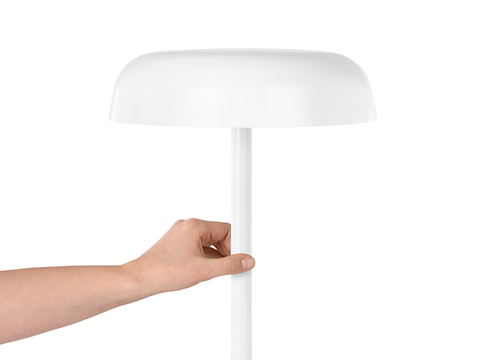 A hand touches the stem of a white Ode Lamp to turn it on or off.